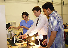 Image: Niloufar Fekerarad, Ray England and Navin Viswanathan look over a fuel cell experiment.